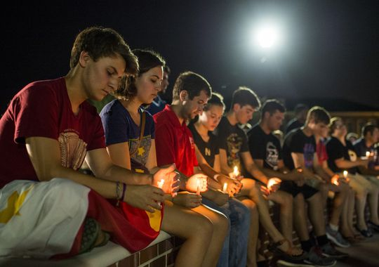 Students gather to mourn during a candlelight vigil for the Grand 16 Theatre shooting victims at the University of Louisiana at Lafayette in Lafayette, La. Credit: Associated Press, Paul Kieu