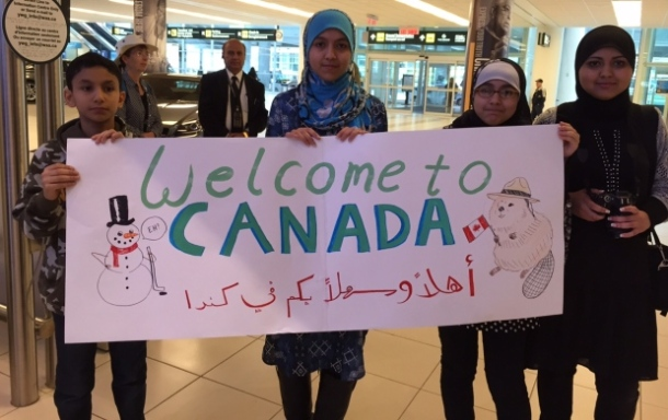 "From CBC: ""When 24 Syrian refugees arrived in Winnipeg in October, relatives greeted them with signs, hugs and presents."" Photo: Angela Johnston/CBC"